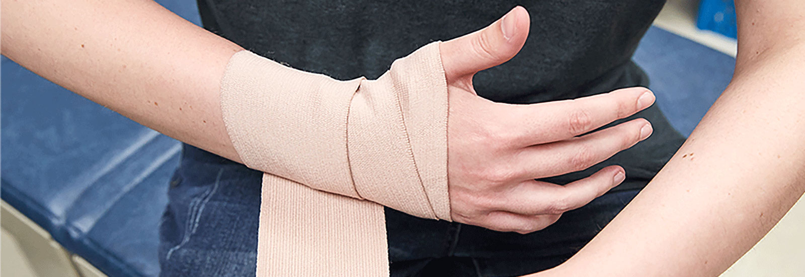 person wrapping bandage around sprained wrist