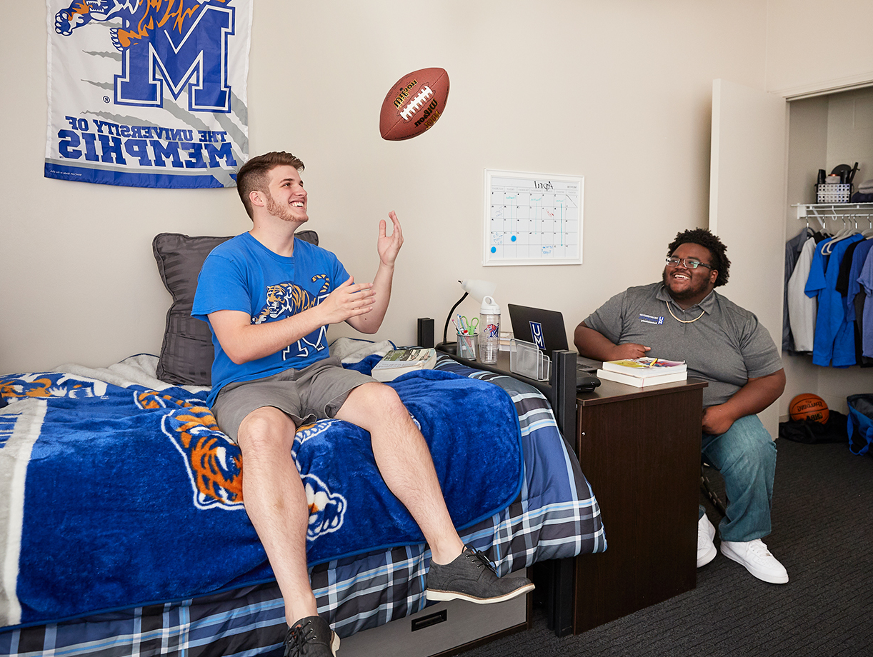 two male students hanging out in dorm room